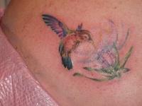 Paint splash hummingbird and flower tattoo